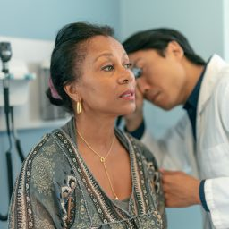 woman getting her ears checked by a doctor