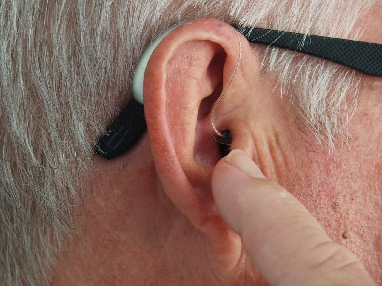 Man points at his hearing aid.