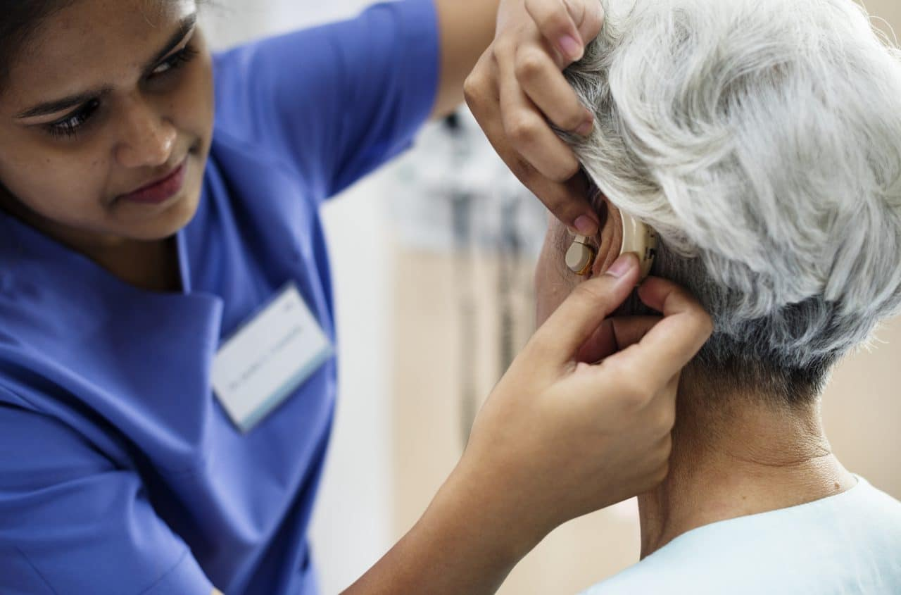 An older woman getting fitted with a hearing aid.